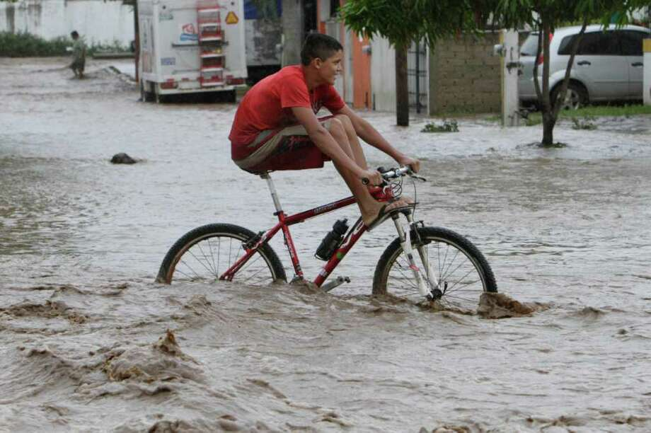A resident rides a bike through a flooded street in Villa de Coral, Mexico, Wednesday Oct. 12, 2011. Hurricane Jova slammed into Mexico's Pacific coast as a Category 2 storm early Wednesday, killing at least two people and injuring some six, while a tropical depression hit farther south and unleashed steady rains that contributed to 13 deaths across the border in Guatemala. Photo: AP