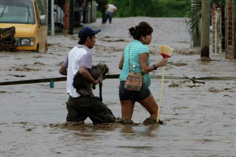 Residents wade through a flooded street in Villa de Coral, Mexico, Wednesday Oct. 12, 2011. Hurricane Jova slammed into Mexico's Pacific coast as a Category 2 storm early Wednesday, killing at least two people and injuring some six, while a tropical depression hit farther south and unleashed steady rains that contributed to 13 deaths across the border in Guatemala. Photo: AP