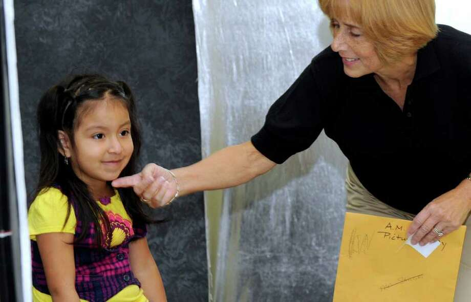 Nicole Lima, left, is coaxed to raise her chin for her school photo by kindergarten teacher Roberta Struski at Pembroke School in Danbury. Photo taken Monday, Oct. 3, 2011. Photo: Carol Kaliff
