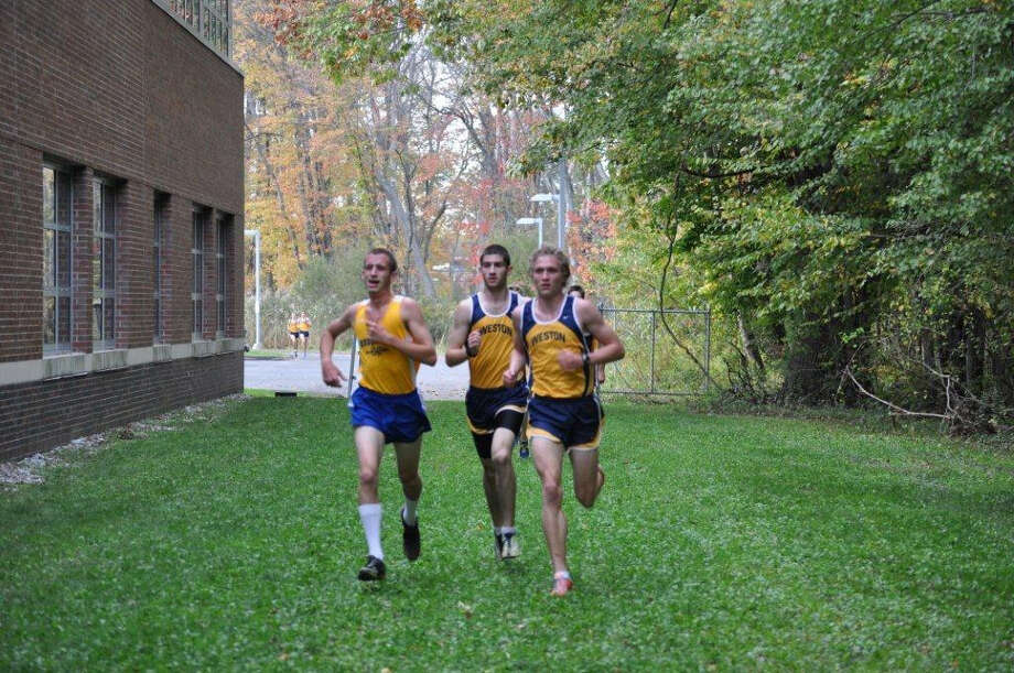 Weston's Noah Krassin, center, and David Stankiewicz, right, jockey for position with Brookfield's Jacob Meyerson, left, Tuesday in a quad-meet at Weston. Stankiewicz won the race, Krassin places second and Meyerson took third as the Trojans swept the meet, which included a 26-29 victory over Brookfield. Photo: Contributed Photo