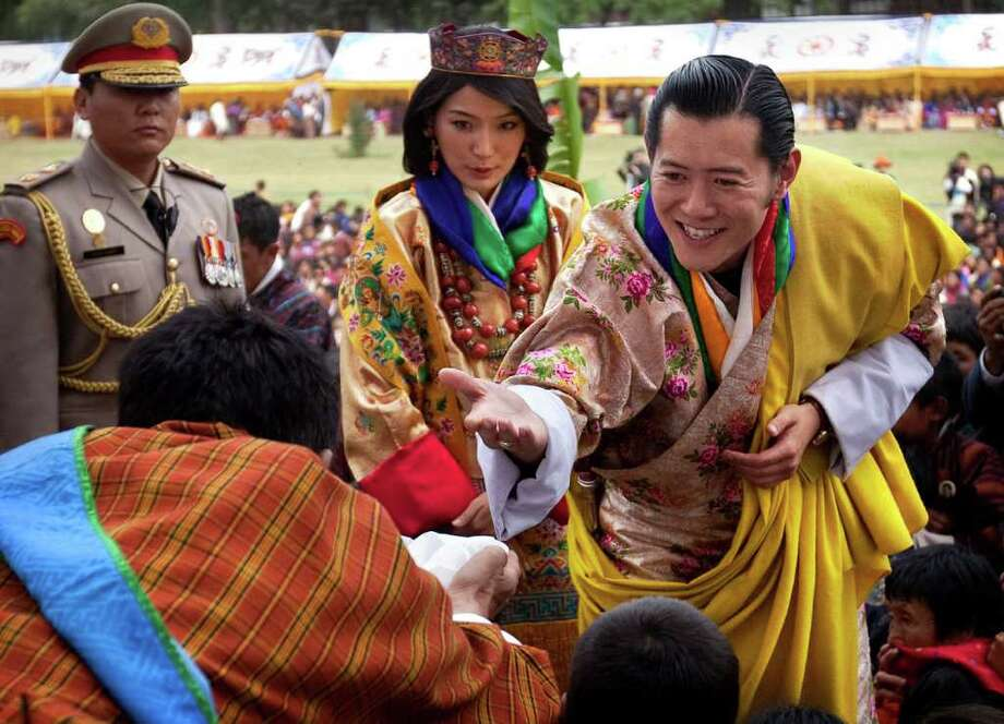 King Jigme Khesar Namgyal Wangchuck, right, Queen Jetsun Pema, center, greet locals during a celebration after they were married at the Punakha Dzong in Punakha, Bhutan. The 31-year-old reformist monarch of the small Himalayan Kingdom wed his commoner bride in a series ceremonies in the 17th century monastic fortress. Photo: Kevin Frayer, Associated Press / AP