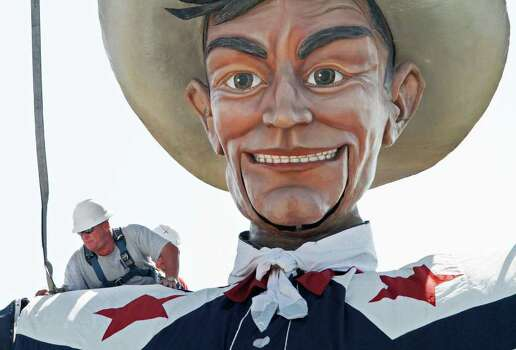 "Gene Baker, with the State Fair, leans out on the shoulder of Big Tex to unfasten the lift cables on the north end of the State of Texas Fair's Midway in Dallas, Monday, Sept. 26, 2011. The 2011 State Fair, ""A Timeless Tradition"", is also the 125th anniversary of the Fair in Dallas. (AP Photo/Fort Worth Star-Telegram, Paul Moseley) Photo: Paul Moseley / Fort Worth Star-Telegram"