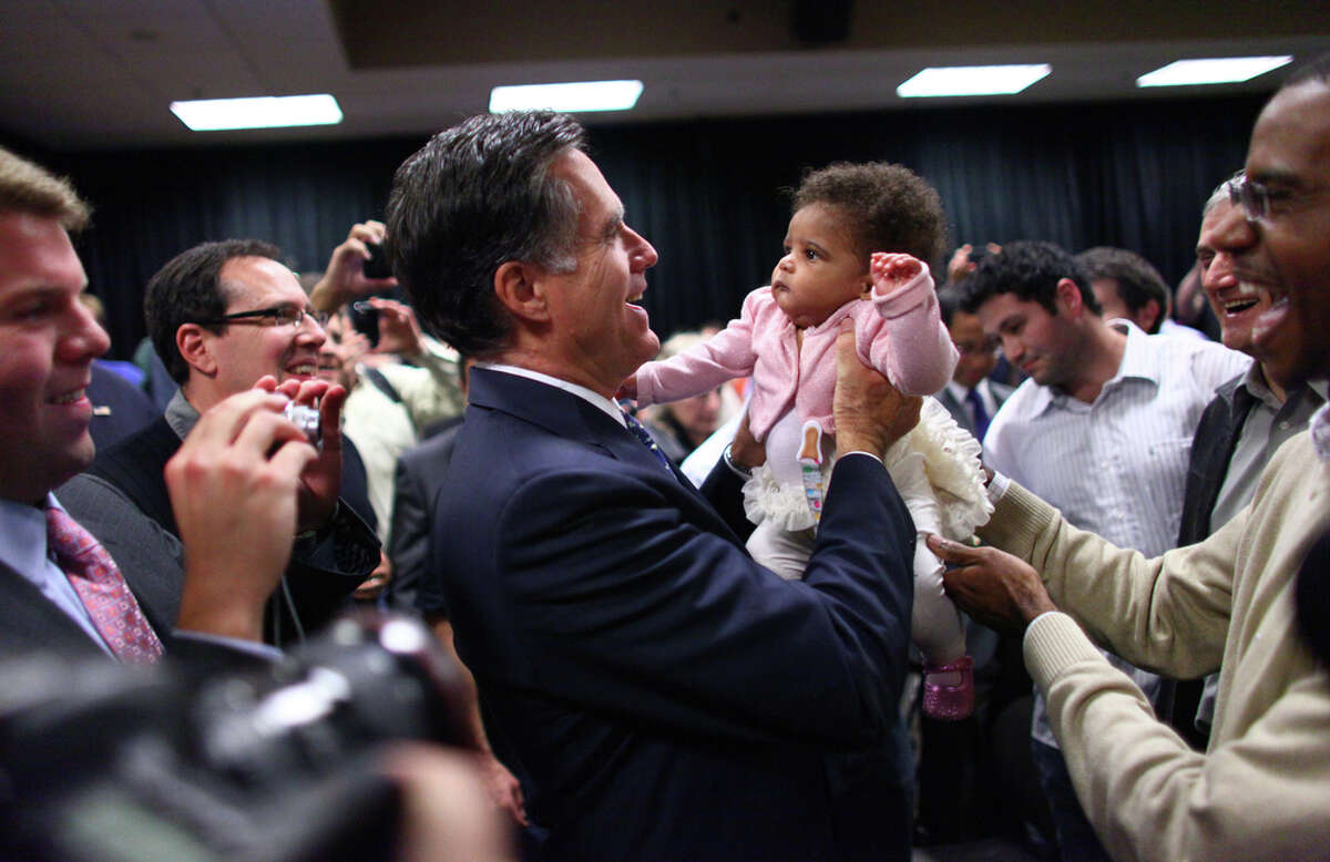 Presidential candidate Mitt Romney lifts Alexandria McDonald, 6 months, daughter of Microsoft employee Orville McDonald, far right, after a speech on Thursday, October 13, 2011 on the Microsoft campus in Redmond. The Republican presidential candidate came to Microsoft as part of a speaker series and talked about trade policy.