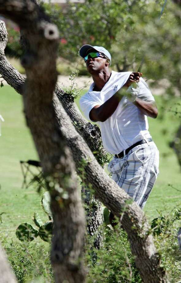 Former San Antonio Spurs Sean Elliott gets out of wooded area off the No. 1 fairway during the Championship Pro Am at the AT&T Championship tournament at the TPC Canyon Course, Thursday, Oct. 13, 2011.  JERRY LARA/glara@express-news.net Photo: JERRY LARA, Express-News / SAN ANTONIO EXPRESS-NEWS