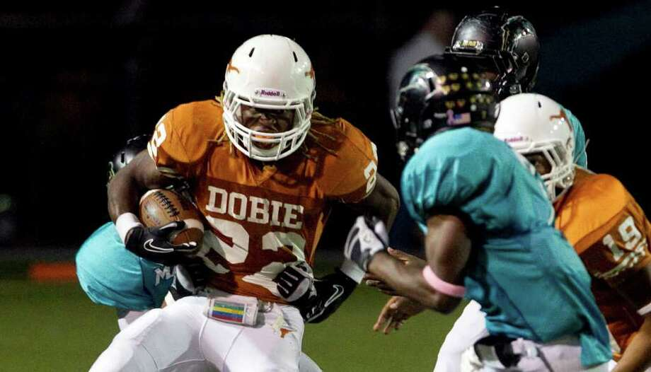 Dobie 49, Pasadena Memorial 37 Dobie High School running back Andrew Robinson (22), tries to get away from the Pasadena Memorial defense in the third quarter of a District 22 5-A football game Thursday, Oct. 13, 2011, at Veterans Memorial Stadium in Pasadena. Photo: Nick De La Torre, Houston Chronicle / © 2011  Houston Chronicle