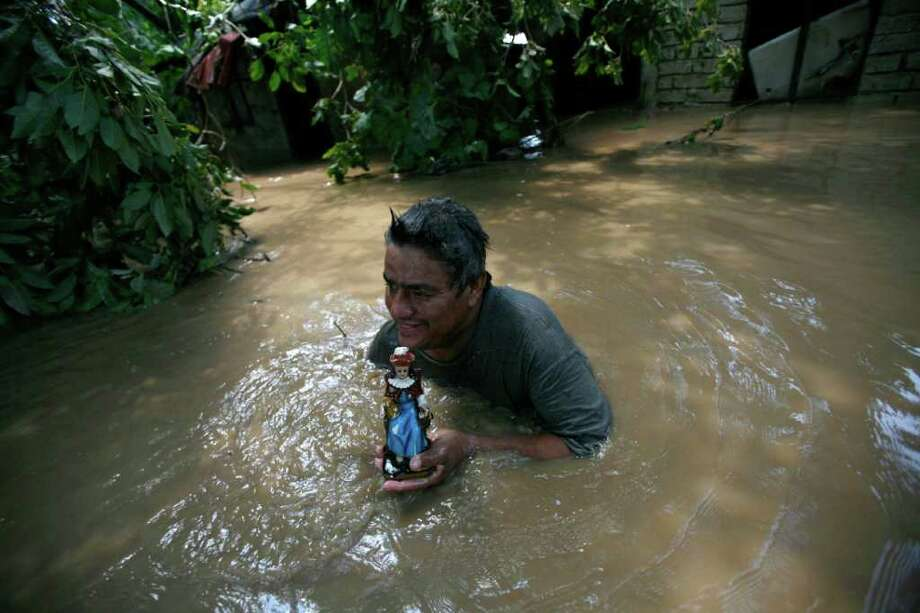 David Martinez holds a statue of Saint Nino de Atocha after recovering it from his flooded home in El Chavarin, Colima state, Mexico, Thursday, Oct. 13, 2011. Mexican authorities on Thursday raised to six the death toll from Hurricane Jova, which hit along the Pacific coast as a Category 2 storm, and warned the storm's remnants could affect opening ceremonies of the Pan American Games. Photo: Marco Ugarte, Associated Press / AP
