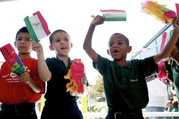 """Adrian Sandoval, Julio Beltran and Jamarri Ardison cheer Thursday afternoon October 13, 2011 as students at Varnett Public Elementary School don """"Hispanic"""" attire and take part in a parade around the school parking lot to celebrate National Hispanic Heritage Month."""