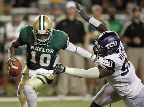 RON JENKINS: McCLATCHY-TRIBUNE CATCH HIM IF YOU CAN: Much like TCU's Stansly Maponga (90) in the season opener, Texas A&M players face a tough task in trying to get their hands on Baylor's elusive Robert Griffin III (10) on Saturday at Kyle Field. Photo: Ron Jenkins / Fort Worth Star-Telegram