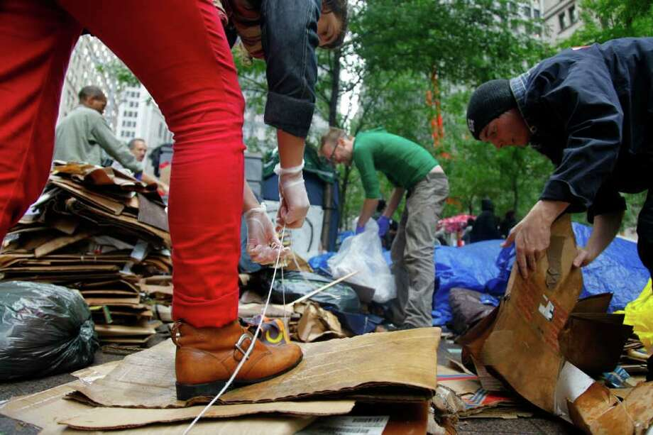 "Workgroups at Zuccotti Park's ""Occupy Wall Street"" encampment collect trash on Thursday, Oct. 13, 2011 in New York.   The owner of the private park where ""Occupy Wall Street"" protesters have been camped out for nearly a month in lower Manhattan gave notice Thursday that it will begin enforcing regulations that prohibit everything from lying down on benches to storing personal property on the ground. The landlord, Brookfield Properties, handed out a notice to protesters saying they would be allowed back inside after a planned park cleanup on Friday morning if they abide by park regulations. (AP Photo/Bebeto Matthews) Photo: Bebeto Matthews"