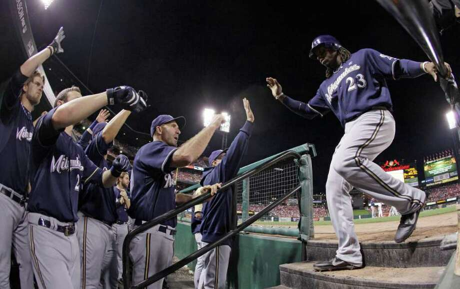 Milwaukee Brewers' Rickie Weeks is congratulated after scoring on a ball hit by George Kottaras during the sixth inning. Photo: Matt Slocum / AP