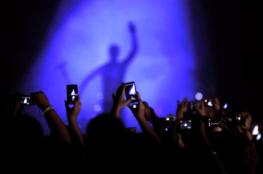 "Singer Enrique Iglesias makes his entrance as people make pictures during his ""Euphoria"" tour at the AT&T Center on Thursday, Oct. 13, 2011. Photo: Billy Calzada/gcalzada@express-news.net / gcalzada@express-news.net"
