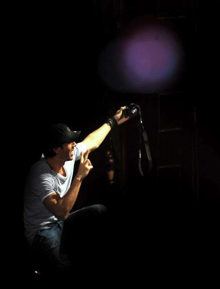 Enrique Iglesias takes a picture of himself with a fan's camera during his performance at the AT&T Center on Thursday, Oct. 13, 2011. Photo: Billy Calzada/gcalzada@express-news.net / gcalzada@express-news.net