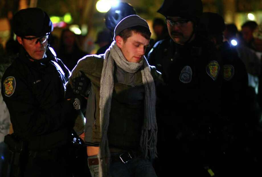 Seattle Police arrest an Occupy Seattle protester at Seattle's Westlake Park on Thursday, October 13, 2011. Ten protesters were arrested for refusing to move from a makeshift structure in the park. Earlier city officials said that people needed to clear from the park at 10 p.m. when it closes. Eventually police withdrew, causing the crowd gathered to erupt in cheers. Photo: JOSHUA TRUJILLO / SEATTLEPI.COM