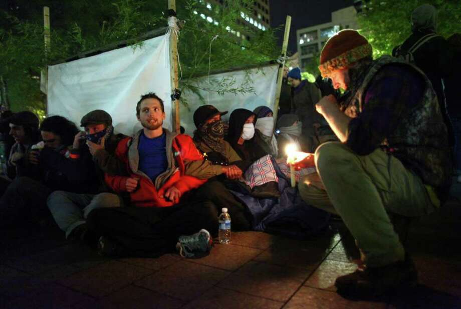 Occupy Seattle protesters prepare to be arrested by Seattle police at Westlake Park on Thursday, October 13, 2011. Ten protesters were arrested for refusing to move from a makeshift structure in the park. Earlier, city officials said that people needed to clear from the park at 10 p.m. when it closes Photo: JOSHUA TRUJILLO / SEATTLEPI.COM
