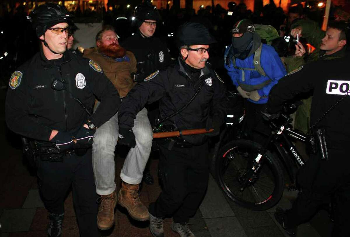 Seattle Police carry away an Occupy Seattle protester at Seattle's Westlake Park on Thursday, October 13, 2011. Ten protesters were arrested for refusing to move from a makeshift structure in the park. Earlier city officials said that people needed to clear from the park at 10 p.m. when it closes. Eventually police withdrew, causing the crowd gathered to erupt in cheers.