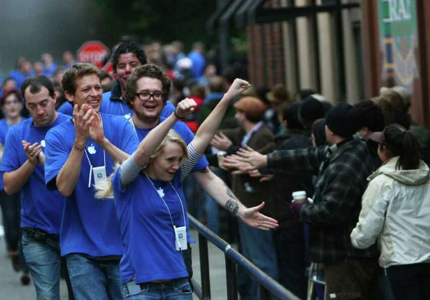 Apple Store employees run and cheer as they prepare to take the first customers at the University Vi