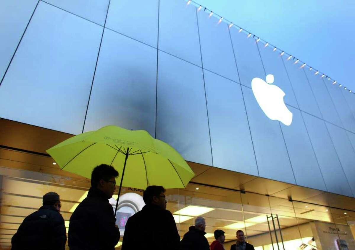 Customers brave a light rain, waiting for the University Village Apple Store in Seattle to open on Friday, October 14, 2011. Customers lined up for the new iPhone 4S.