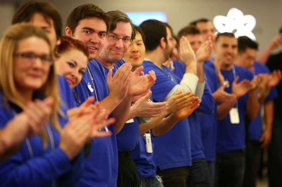 Apple Store employees cheer as they prepare to take the first customer at the University Village Apple Store in Seattle. Customers lined up for the new iPhone 4S. Photo: JOSHUA TRUJILLO / SEATTLEPI.COM