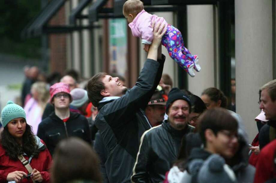 Beau Hunter hoists his 9 month-old daughter Berit as he waits in line with other customers at the University Village Apple Store. Photo: JOSHUA TRUJILLO / SEATTLEPI.COM