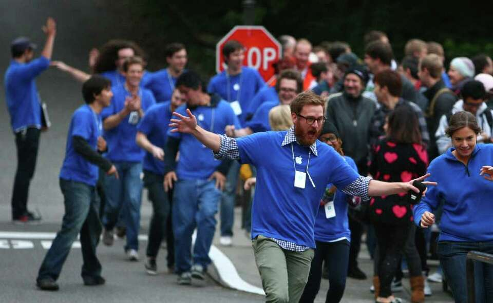 Apple Store employees run and cheer as they prepare to take the first customers for the new iPhone 4