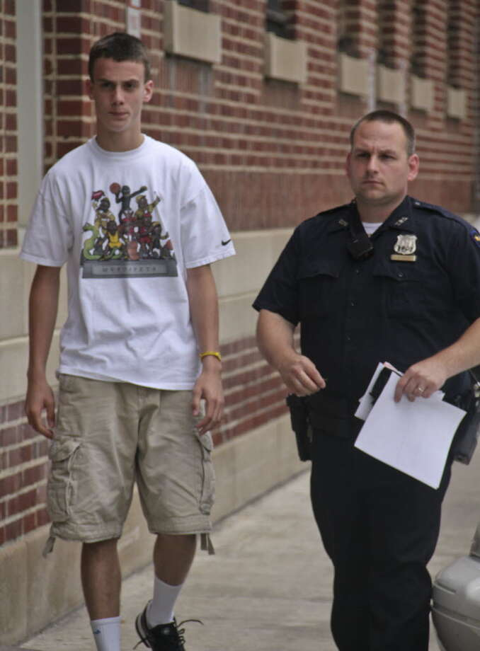 Patrick Chamberlain, 16, of Wynantskill, left, leaves the Troy City Police station, accompanied by an officer after posting bail on Friday, July 8, 2011. Chamberlain was charged with two counts of felony gang assault. (Erin Colligan / Special To The Times Union)