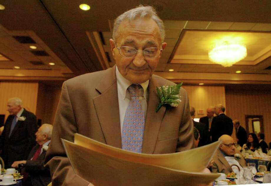 Attorney Joe Mirsky looks at old photos at the Greater Bridgeport Bar Association luncheon in March of 2008. The event honored members who were members of the Connecticut Bar for over fifty years. Photo: File Photo / Connecticut Post File Photo
