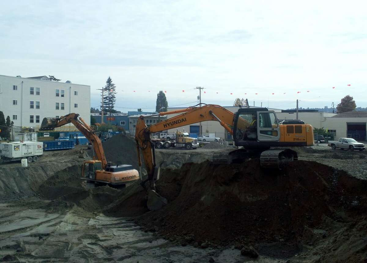 Workers excavate the site of an apartment building under construction along Market Street in Seattle's Ballard neighborhood on Oct. 14, 2011.