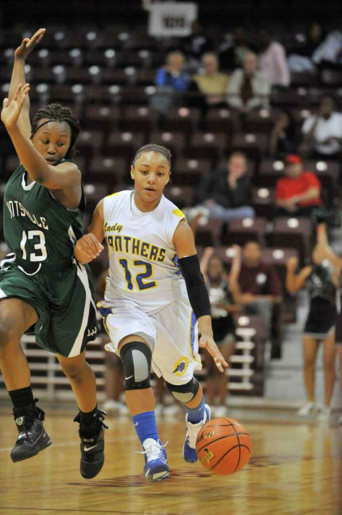 Ozen guard Asia Booker races up court against Huntsville defender Ceidra Coleman in the final minutes of the second half of their Class 4A regional final playoff matchup at the Aldine Campbell Center in Aldine. Saturday, February 26, 2011. Valentino Mauricio/The Enterprise