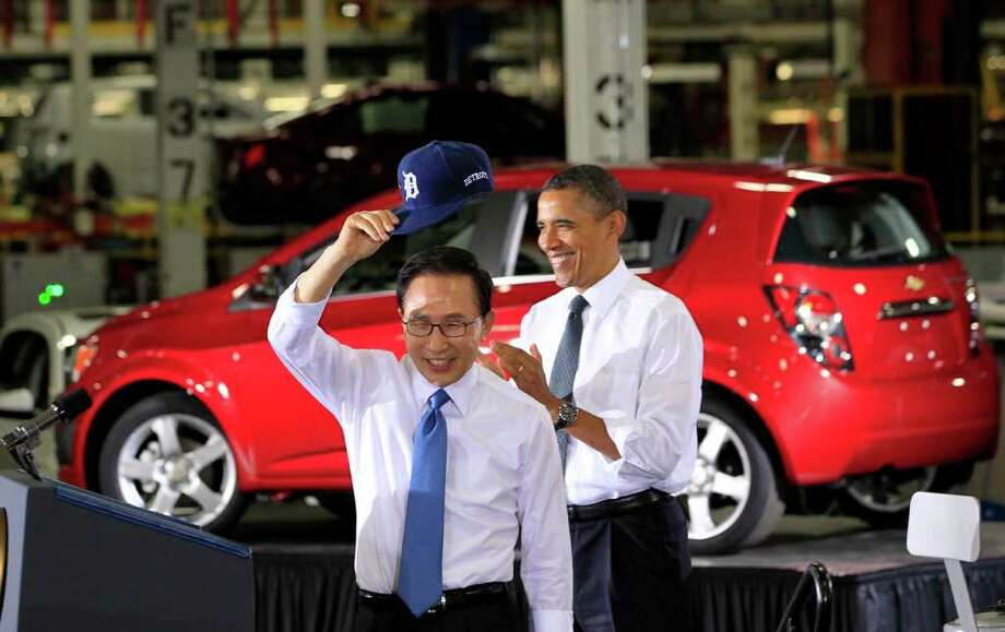 Lee Myung-bak, president of South Korea, left, tips his Detroit Tigers baseball cap to the audience as he arrives to speak with U.S. President Barack Obama at the General Motors Co. (GM) Orion Assembly Plant in Orion Township, Michigan, U.S., on Friday, Oct. 14, 2011. The U.S.-Korea free trade agreement will help create jobs, Obama said after a tour of the plant with Lee. Photo: Jeff Kowalsky, Bloomberg / © 2011 Bloomberg Finance LP