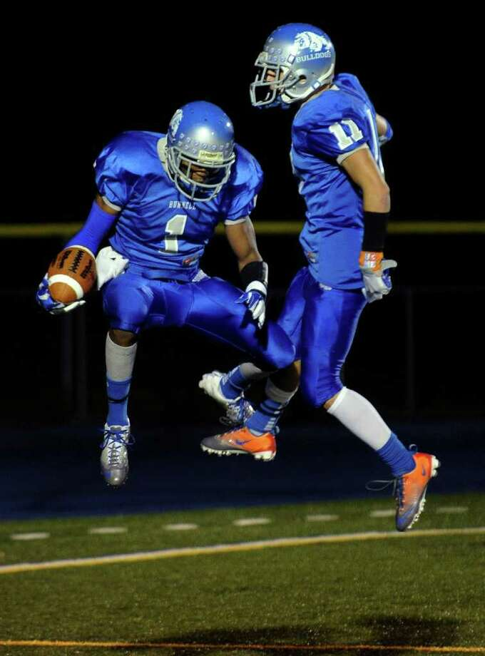 Bunnell's #1 Jawad Chisholm, left, leaps up to celebrate his touchdown with teammate #11 Jared Vasquez, during boys football action against Pomperaug in Stratford, Conn. on Friday October 14, 2011. Photo: Christian Abraham / Connecticut Post