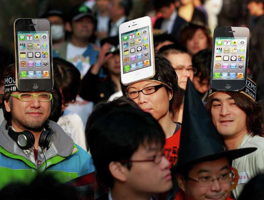 Apple Inc. fans wait in line in front of a shop in Tokyo to buy its new iPhone 4S on the launch day in Japan Friday, Oct. 14, 2011. Photo: Itsuo Inouye, Associated Press / AP