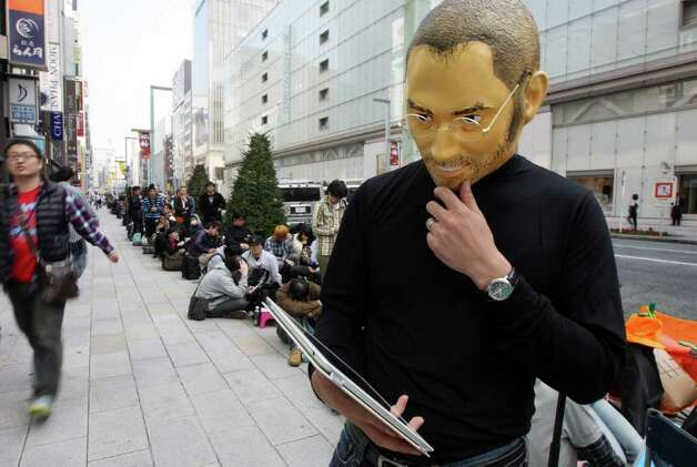 A customer wearing a mask of Steve Jobs, co-founder and former chief executive officer of Apple Inc., waits in line outside the company's shop in the Ginza district of Tokyo, Japan, on Friday, Oct. 14, 2011. Photo: Tomohiro Ohsumi, Bloomberg / 2011 Bloomberg Finance L.P.