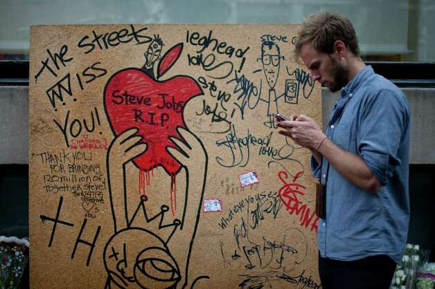 A man walks past a memorial to Steve Jobs, co-founder and former chief executive officer of Apple Inc., outside of a store in New York, U.S., on Friday, Oct. 14, 2011. Photo: Scott Eells, Bloomberg / © 2011 Bloomberg Finance LP