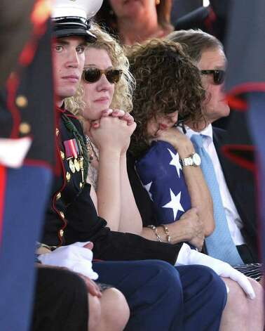 Becky Whetstone hugs an American flag during services for her son LCpl. Benjamin Schmidt at Sam Houston National Cemetery Friday Oct. 14, 2011.  At left, Whetstone's daughter and the Schmidt's sister,  Casey Schmidt, sits next to a U.S. Marine escort.  At far right is John Cheairs. Schmidt was killed in action on October 6 while on patrol in Afghanistan.  The 24-year-old was a graduate of Alamo Heights High School and attended Texas Christian University.  He was stationed out of Camp Pendleton, California.  Serving his second tour in Afghanistan, Schmidt deployed in September with the 2nd Battalion, 4th Marine Regiment. Photo: HELEN L. MONTOYA, Helen L. Montoya/hmontoya@express-news.net / SAN ANTONIO EXPRESS-NEWS