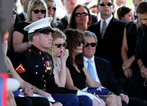Becky Whetstone, at right,  sits with an American flag during services for her son LCpl. Benjamin Schmidt at Sam Houston National Cemetery Friday Oct. 14, 2011.  At left, Whetstone's daughter and the Schmidt's sister,  Casey Schmidt, sits next to a U.S. Marine escort.  At far right is John Cheairs. Schmidt was killed in action on October 6 while on patrol in Afghanistan.  The 24-year-old was a graduate of Alamo Heights High School and attended Texas Christian University.  He was stationed out of Camp Pendleton, California.  Serving his second tour in Afghanistan, Schmidt deployed in September with the 2nd Battalion, 4th Marine Regiment. Photo: HELEN L. MONTOYA, Helen L. Montoya/hmontoya@express-news.net / SAN ANTONIO EXPRESS-NEWS