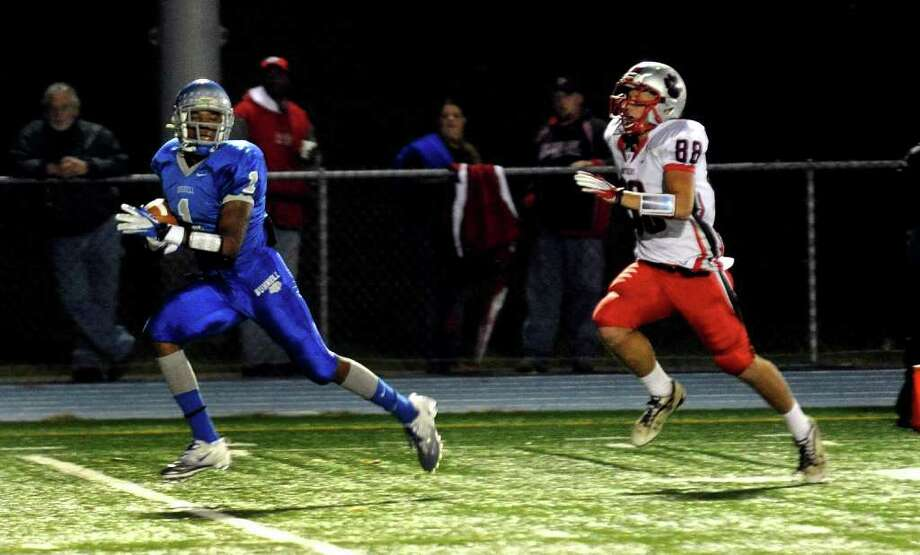 Highlights from boys football action between Bunnell and Pomperaug in Stratford, Conn. on Friday October 14, 2011. Bunnell's #1 Jawad Chisholm, left, carries the ball to the endzone for a touchdown as Pomperaug's #88 Brett Gaughan gives chase. Photo: Christian Abraham / Connecticut Post