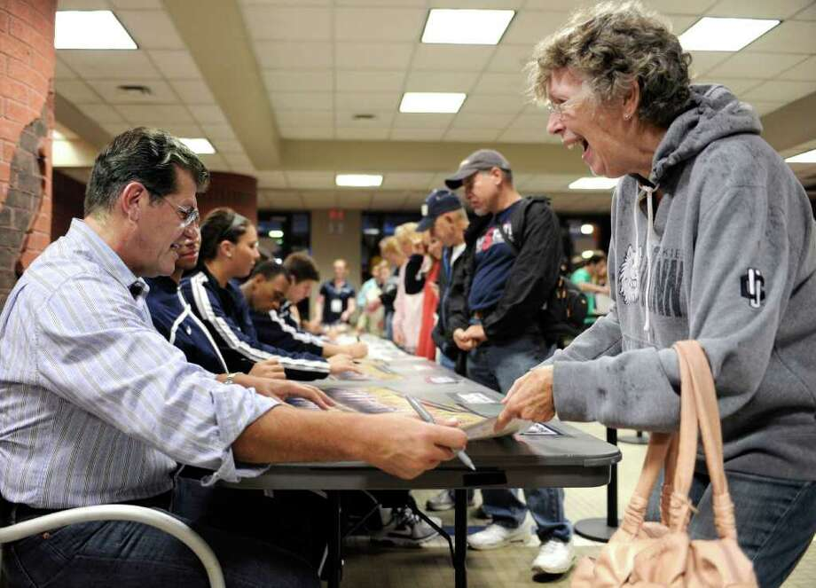 Sheila Dickey, right, of Portland, Conn., reacts as Connecticut head coach Geno Auriemma hands her an autograph at a men's and women's basketball team autograph session during First Night NCAA college basketball exhibition, in Storrs, Conn., Friday, Oct. 14, 2011.  (AP Photo/Jessica Hill) Photo: Jessica Hill, AP / AP2011
