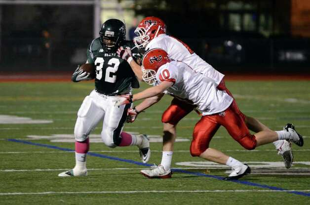 Norwalk's Tomar Joseph (32) carries the ball for yardage as New Canaan's Jake Miller (10) and Dylan Leeming (14) defend during the football game at Norwalk High School on Friday, Oct. 14, 2011. Photo: Amy Mortensen / Connecticut Post Freelance