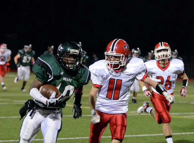 Norwalk's Andy St. Fleur (10) carries the ball as New Canaan's Patrick Burke (11) defends during the football game at Norwalk High School on Friday, Oct. 14, 2011. Photo: Amy Mortensen / Connecticut Post Freelance