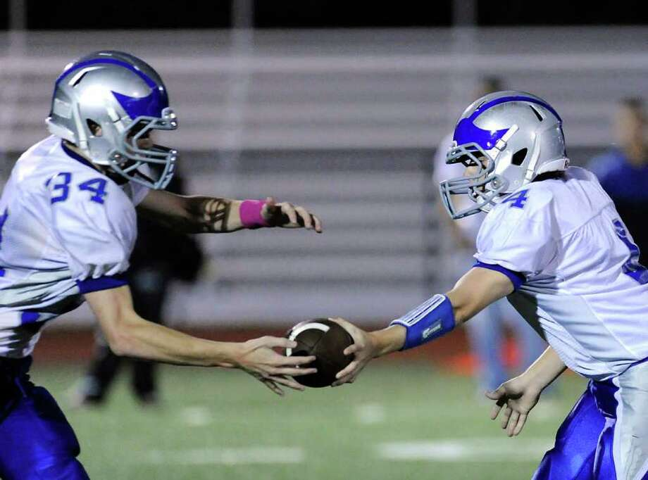 Running back Jim Gasper, #34 of Fairfield Ludlowe High School takes the handoff from his QB Matt White, # 4, during football game between Greenwich High School and Fairfield Ludlowe High School at Greenwich, Friday night, Oct. 14, 2011. Photo: Bob Luckey / Greenwich Time