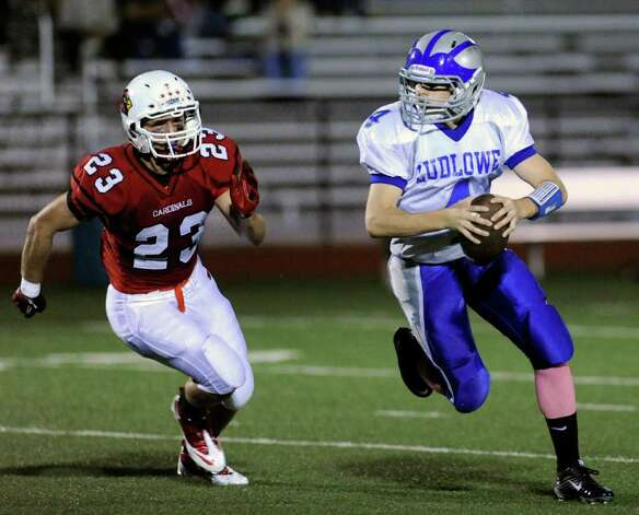 At right, Fairfield Ludlowe quarterback Matt White, # 4, is pursued by Mike Daly, # 23 of Greenwich High School during High school football game between Greenwich High School and Fairfield Ludlowe High School at Greenwich, Friday night, Oct. 14, 2011. Photo: Bob Luckey / Greenwich Time