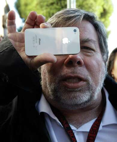 Apple co-founder Steve Wozniak holds up his new Apple iPhone 4S at the Apple store in Los Gatos, Calif., Friday, Oct. 14, 2011. Woziak waited 20 hours in line to be the first Apple customer at the Los Gatos Apple store to buy the new iPhone 4S. (AP Photo/Paul Sakuma) Photo: Paul Sakuma