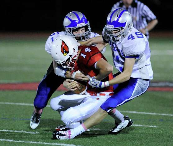 Greenwich QB Liam O'Neil, # 14, is sacked by Fairfield Ludlowe's Kyle Dammeyer, # 49 and a teammate during High school football game between Greenwich High School and Fairfield Ludlowe High School at Greenwich, Friday night, Oct. 14, 2011. Photo: Bob Luckey / Greenwich Time