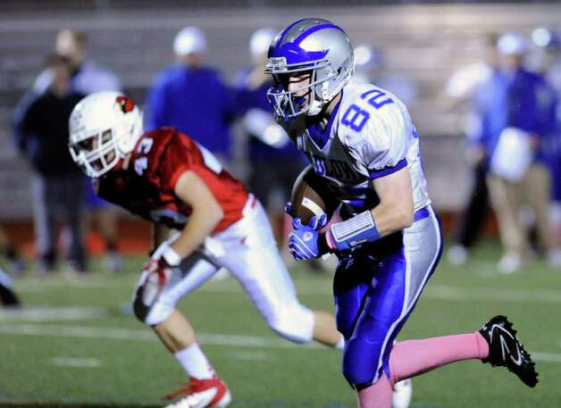 At right, Victor D'Ascenzo, # 82, of Fairfield Ludlowe High School, scores a touchdown during High school football game between Greenwich High School and Fairfield Ludlowe High School at Greenwich, Friday night, Oct. 14, 2011. In the background is Mike Longo of Greenwich on the pursuit. Photo: Bob Luckey / Greenwich Time