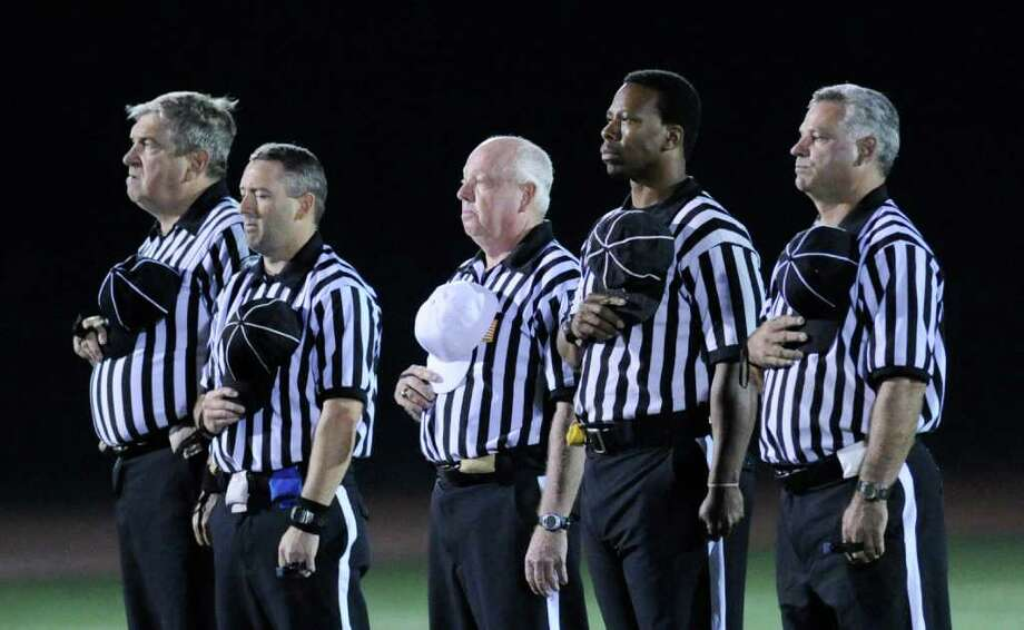 The referees during the National Anthem, high school football game between Greenwich High School and Fairfield Ludlowe High School at Greenwich, Friday night, Oct. 14, 2011. Photo: Bob Luckey / Greenwich Time