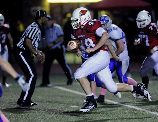 Shane Nastahowski, # 48 of Greenwich High School runs for a first quarter touchdown during High school football game between Greenwich High School and Fairfield Ludlowe High School at Greenwich, Friday night, Oct. 14, 2011. Pursuing on the play for Fairfield Ludlowe High School is Ben Brzoski, # 56 and Bob Decker, # 77 of Greenwich. Photo: Bob Luckey / Greenwich Time