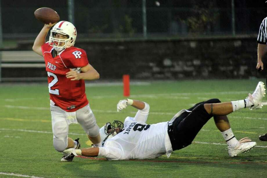 Fairfield Prep QB Thomas Brewster, right, goes to pass the ball before Xavier's #9 Jovan Knox can completely tackle him, during boys football action at Fairfield University in Fairfield, Conn. on Friday October 14, 2011. Photo: Christian Abraham / Connecticut Post