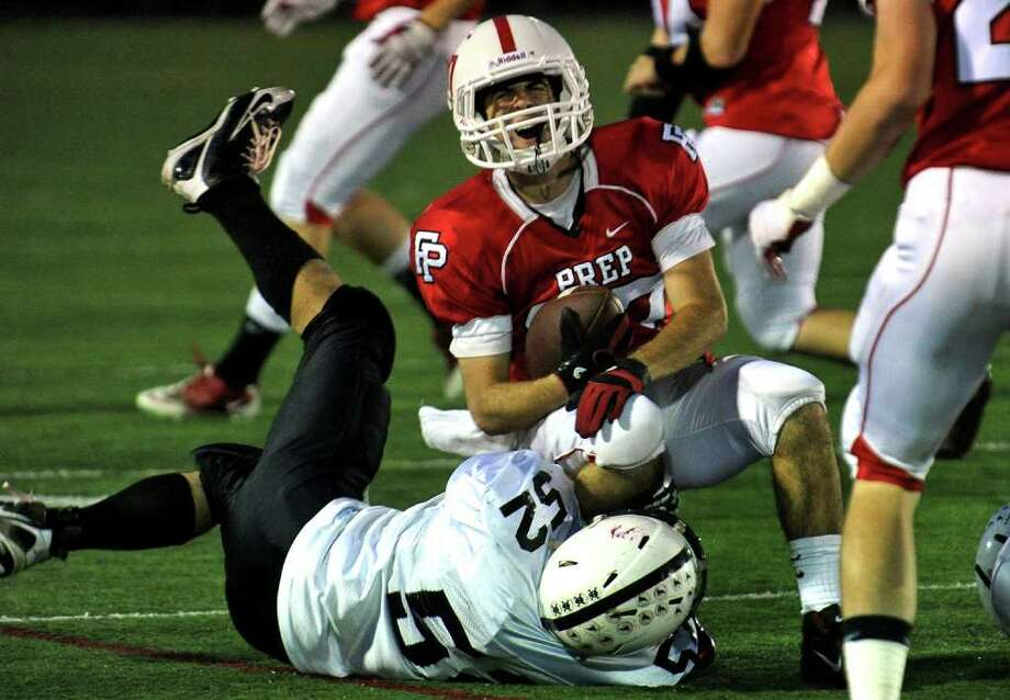 Fairfield Prep's #37 Joseph McBride gets injured as he is tackled by Xavier's #52 Ryan Craig, during boys football action at Fairfield University in Fairfield, Conn. on Friday October 14, 2011. Photo: Christian Abraham / Connecticut Post