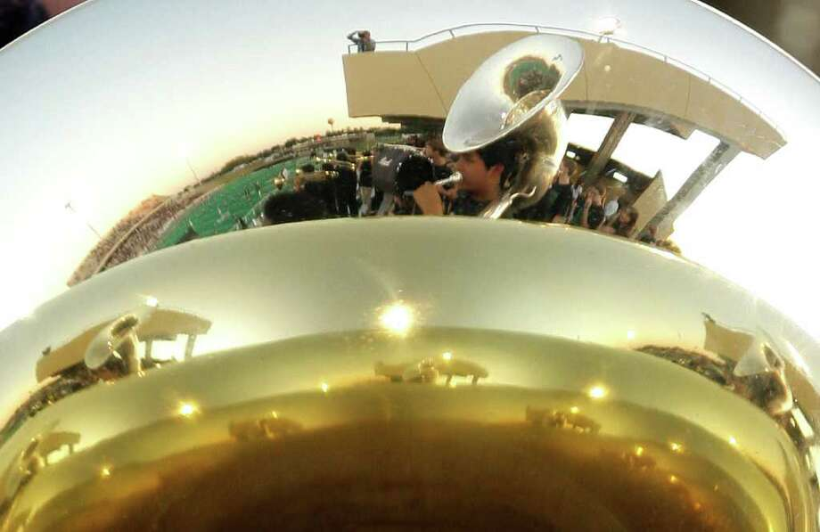 10/14/11: The Cy Falls reflection is seen in a tuba while the marching band warms up before the Cy Falls Eagles played against the Cy Fair Bobcat's in a high school District 17-5A football game at Pridgeon Stadium in Houston, Texas. For to Chronicle :Thomas B. Shea Photo: For To Chronicle :Thomas B. Shea