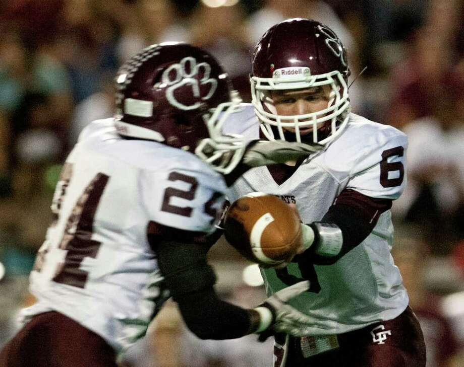 Cy-Fair 24, Cy Falls 17 10/14/11: Quarterback Logan Taylor #6  hands the ball off to running back John Jacob #24 of the Cy Fair Bobcat's as he rushes against the Cy Falls Eagles  in a high school District 17-5A football game at Pridgeon Stadium in Houston, Texas. For to Chronicle :Thomas B. Shea Photo: For To Chronicle :Thomas B. Shea